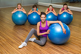 Fitness class posing with exercise balls in studio