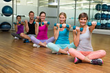 Fitness class sitting and holding dumbbells