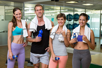 Fit man and women smiling at camera in studio
