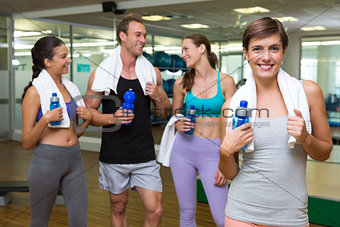 Fit woman smiling at camera in busy fitness studio