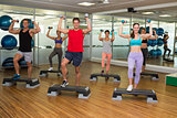 Fitness class doing step aerobics with dumbbells