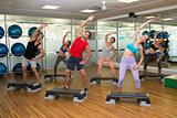 Fitness class doing step aerobics