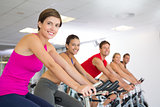Spin class working out and smiling at camera
