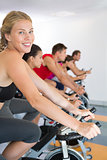 Blonde smiling at camera during spin class