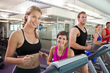 Trainer and clients smiling at camera on the treadmill