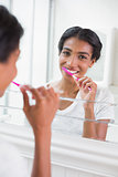 Pretty woman brushing her teeth