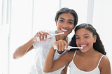 Pretty mother brushing her teeth with her daughter