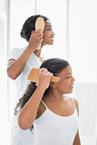 Mother and daughter brushing their hair together