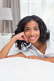 Pretty woman smiling at camera lying on bed