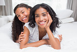 Pretty woman lying on bed with her daughter smiling at camera