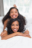 Smiling mother and daughter posing together on bed