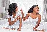 Mother and daughter having an argument on bed