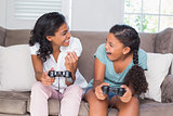 Happy mother and daughter playing video games together on sofa