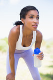 Fit woman holding sports bottle smiling