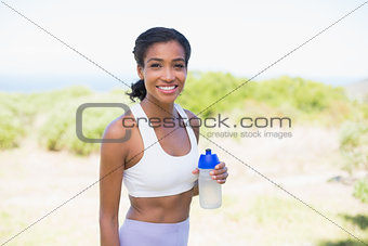 Fit woman holding sports bottle smiling at camera
