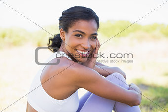 Fit woman sitting on grass smiling at camera