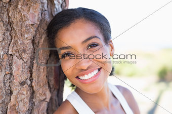 Fit woman leaning against tree smiling at camera