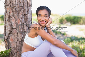 Fit woman sitting against tree smiling at camera
