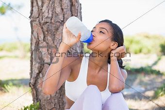 Fit woman sitting against tree drinking from water bottle