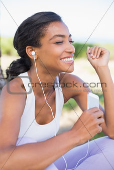 Fit woman sitting down listening to music