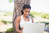 Fit woman sitting against tree using laptop