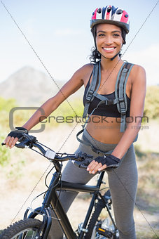 Fit woman going for bike ride smiling at camera