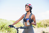 Fit woman going for bike ride holding water bottle
