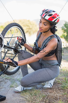 Fit woman fixing the chain on her bike