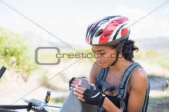 Fit woman holding her injured knee after bike crash