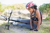 Fit woman lying on ground after bike crash