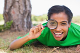 Pretty environmental activist looking at camera through magnifying glass