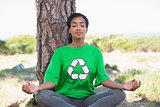 Pretty environmental activist doing yoga by a tree