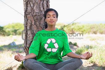 Pretty environmental activist doing yoga by a tree