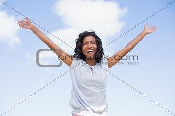 Casual pretty woman standing with arms up
