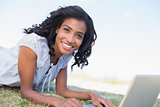 Casual pretty woman lying on the grass using her laptop
