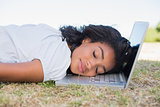 Casual pretty woman lying on the grass sleeping on her laptop