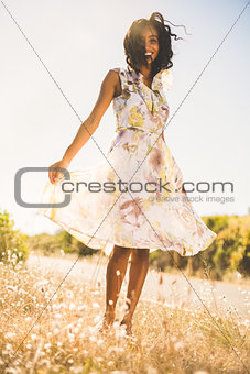 Happy pretty woman standing on the grass in floral dress