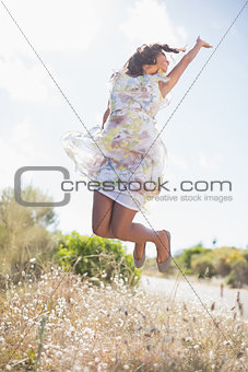Beautiful woman in floral dress jumping up