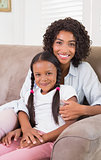 Pretty mother sitting on the couch with her daughter smiling at camera