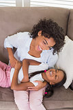 Pretty mother sitting on the couch tickling daughter