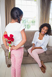 Daughter hiding bouquet of roses for mother on the couch