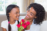 Pretty mother sitting on the couch with her daughter holding roses
