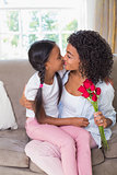 Pretty mother sitting on the couch kissing her daughter holding roses