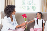 Pretty mother sitting on the couch with her daughter offering roses