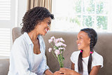 Pretty mother sitting on the couch with her daughter offering flowers