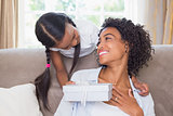 Pretty mother sitting on couch with daughter offering a gift