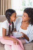 Pretty mother sitting on couch offering daughter a gift