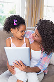 Pretty mother sitting on couch with cute daughter using tablet together
