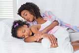 Cute daughter sleeping with mother on the sofa