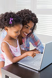 Cute daughter using laptop at desk with mother